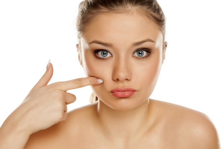 young girl touching her cheek on white background