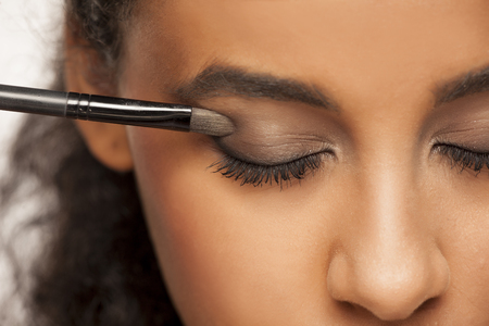 portrait of a young dark-skinned woman applying eye shadow with brush on a white background Stock fotó