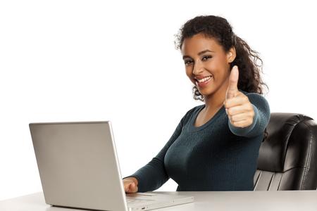 Sonriente y positiva feliz joven afroamericana con rostro hermoso usando computadora portátil, proyecto de trabajo en el escritorio sobre fondo blanco y mostrando los pulgares para arriba