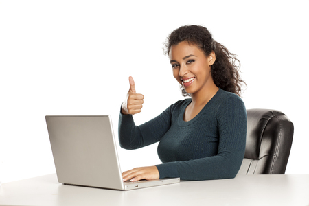 Smiling and positive happy young african-american woman with beautiful face using laptop computer, working project at desk on white background and showing thumbs up