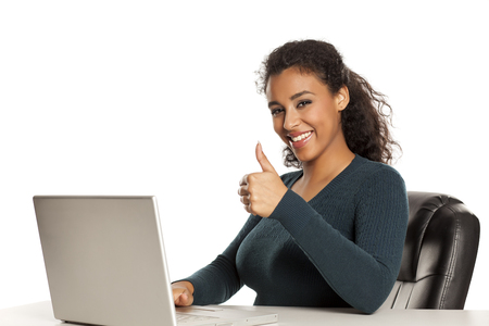Smiling and positive happy young african-american woman with beautiful face using laptop computer, working project at desk on white background and showing thumbs up Stock Photo