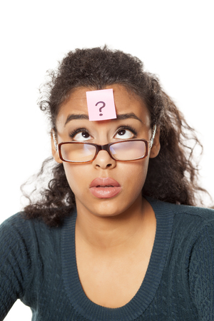 Portrait de jeune femme à la peau sombre confuse avec point d'interrogation sur son front sur fond blanc