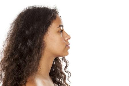 profilo di una giovane donna seria dalla pelle scura senza trucco su sfondo bianco Archivio Fotografico