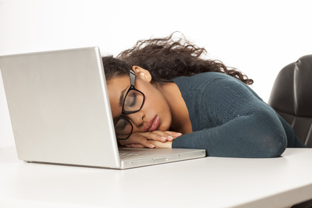 Joven africana cansada deslizándose en su escritorio delante de la computadora portátil sobre fondo blanco.