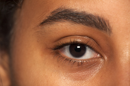 natural eyebrow and eye without makeup of dark skinned female
