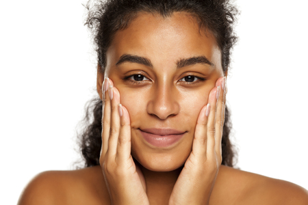 portrait of a happy young dark-skinned woman applying cream on her face on a white background Standard-Bild - 121338526