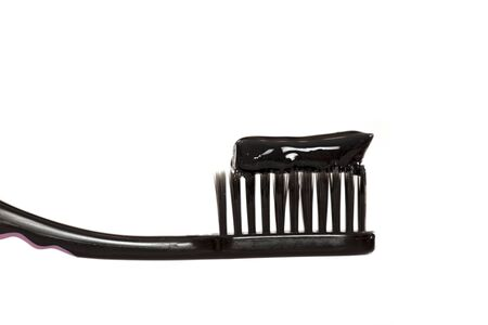 Black tooth paste with active charcoal, and black tooth brush on white background