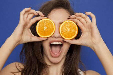Happy young woman posing with slices of oranges on her face on blue background Standard-Bild - 128576198