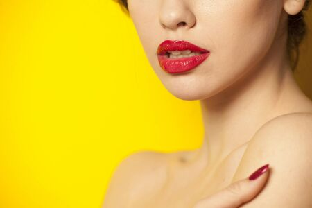 red glossy lipstick on yellow background