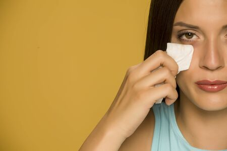 Young woman cleaning her face with wet wipes on yellow background Standard-Bild - 129450235