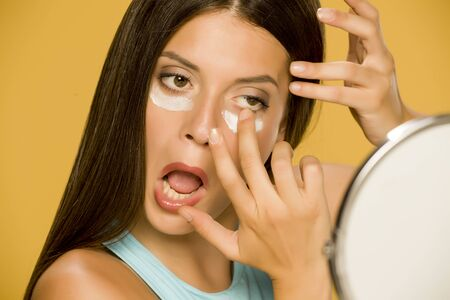 Young woman applying a creme on her  low eyelids on yellow background Standard-Bild - 129450751
