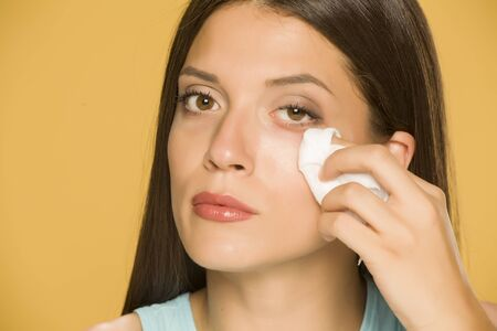 Young woman cleaning her face with wet wipes on yellow background Standard-Bild - 129450757