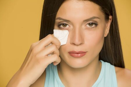 Young woman cleaning her face with wet wipes on yellow background Standard-Bild - 129450762