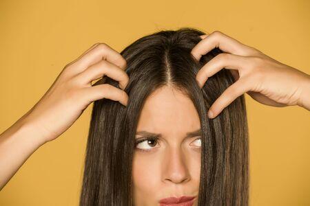 Hermosa mujer joven con picazón en el cuero cabelludo sobre fondo amarillo