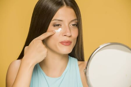 Young smiling woman applying a creme on her  low eyelids on yellow background Standard-Bild - 129450778