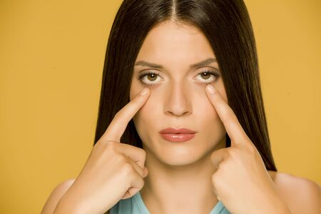 Young woman touching her  low eyelids on yellow background Standard-Bild - 129451273