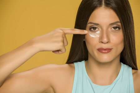 Young woman applying a creme on her  low eyelids on yellow background Standard-Bild - 129451659
