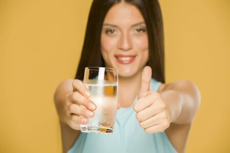 Young smiling woman holding glass of water and showing thumbs up on yellow background