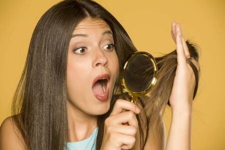 Shocked young woman looking at her hair with magnifying glass on yellow background Standard-Bild - 129451669