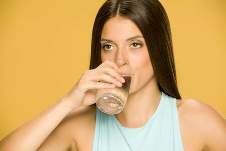 Young smiling woman drinking water from a glass on yellow background