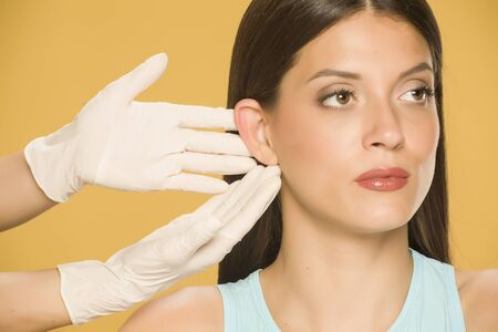 Doctor's hands touching the nose of a young woman on yellow background Standard-Bild - 129451684