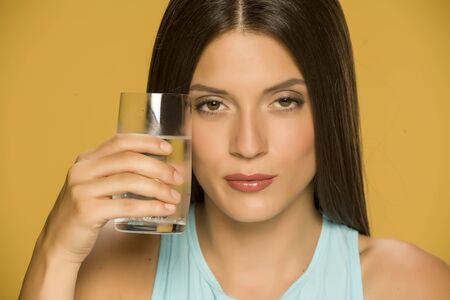 Young woman holding glass of water on yellow background Standard-Bild - 129452037