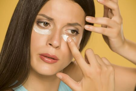 Young woman applying a creme on her  low eyelids on yellow background Standard-Bild - 129452052