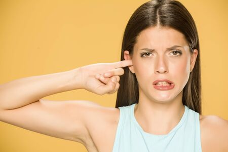 Beautiful young woman with the finger in her ear on yellow background Standard-Bild - 129452072