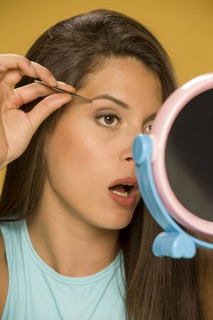 woman plucking her eyebrows with tweezers Standard-Bild - 129554124