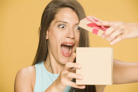 Young happy woman opening a present box on yellow background Standard-Bild - 129554133