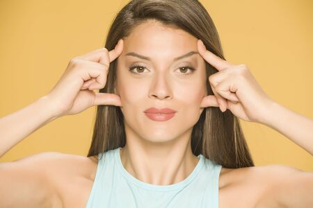 a young woman tightens her face with her hands on a yellow background Standard-Bild - 129554137