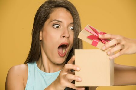 Young shocked woman opening a present box on yellow background Standard-Bild - 129600193