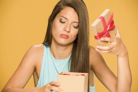 Young disappointed woman opening a present box on yellow background 写真素材