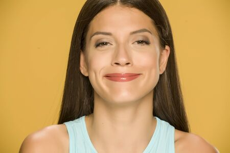 Young woman with fake smile on yellow background Standard-Bild - 129562249