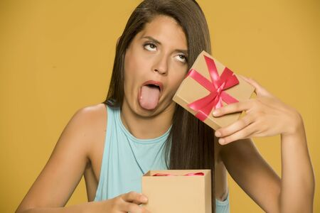 Young disappointed woman opening a present box on yellow background 写真素材 - 129562277