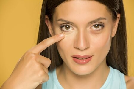 Young woman touching her low eyelids on yellow background