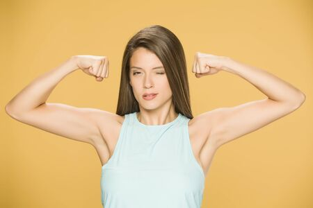 Young woman showing her hands on yellow background Standard-Bild - 129562289