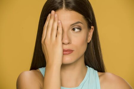 Portrait of beautiful young woman covering one eye with her palm on yellow background Standard-Bild - 129600215