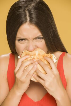Young greedy woman eating a burger on yellow background Standard-Bild - 129600221