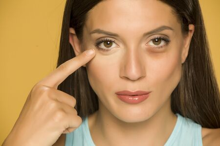 Young woman applying concealer on her  low eyelids on yellow background Standard-Bild - 129600329