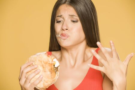 Young greedy woman eating a burger on yellow background