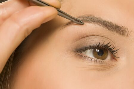 closeuo of woman plucking her eyebrows with tweezers Standard-Bild - 129554498