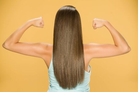 Back view of young woman with long hair, showing her hands on yellow background Standard-Bild - 129554517