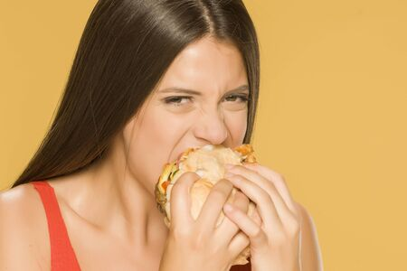 Young greedy woman eating a burger on yellow background Standard-Bild - 129554532