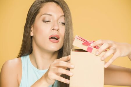 Young beautiful curious woman opening a present box on yellow background Standard-Bild - 129555350