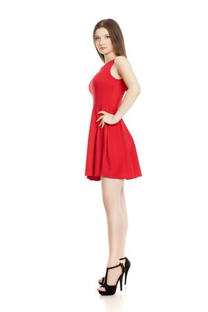 Young woman in short red dress and high heels on white background
