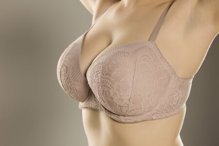 Beautiful big breasts in bra on gray background 写真素材