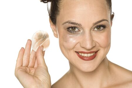 young happy woman cleans her face with cotton pad on white background Stock Photo