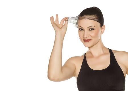 Belle jeune femme posant avec bonnet de perruque sur fond blanc