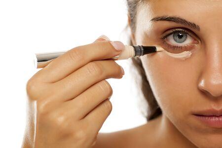 A young woman applies a concealer under the eyes Banco de Imagens